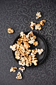 Gilded popcorn on a plate and a patterned tablecloth (seen from above)