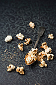Gilded popcorn on a spoon and a patterned tablecloth