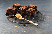 Brownies decorated with gold powder on a wire rack