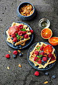Banana waffles with fresh berries, blood oranges and coconut chips