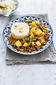 Rindfleischeintopf mit grünen Chilischoten, dazu Reis mit Mais und Erbsen