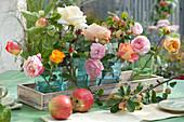 Gläser mit Rosenblüten und Zierapfelzweigen
