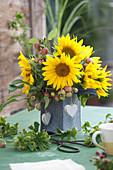 Strauß aus Sonnenblumen und Zieräpfeln in Filztasche