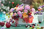 Buntes Herbst-Gesteck mit Rosen, Hagebutten und Phlox