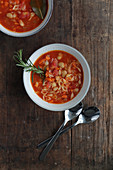 Two bowls of minestrone soup with beans, pasta and sprigs of rosemary