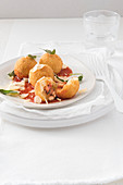 Rice croquettes with sausage centres, on tomato sauce
