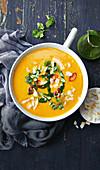 Sweet potato and carrot soup with coriander oil, chili and coconut chips