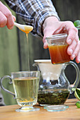 A man adding honey to peppermint tea