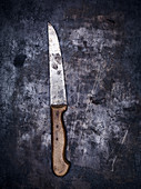 A vintage kitchen knife on a gray metal background (top view)