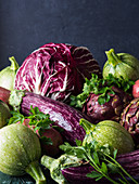 Assortment of raw green and purple vegetables - chicory, red potatoes, zucchini, artichokes and aubergines - on black background