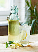 A glass of Elderflower cordial and sparkling water in front of a bottle of Elderflower cordial