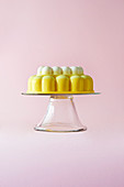 A Lemon Merringue Jelly on a cake stand on a pink background