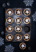 A tray of mince pies decorated with stars dusted with icing sugar on a dark background with Christmas decorations
