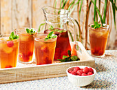 A jug and glasses of Rooibos Iced tea served with raspberies and mint on a wooden tray sitting on a floral table cloth