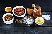 Backzutaten auf Holzuntergrund: Ei, Streusel, Nüsse, Honig, Butter und Mehl