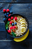 Haferflocken mit Beeren, Mandeln und Banane im Schälchen (Aufsicht)