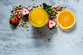 Breakfast ingredients: orange juice, granola and fruits (top view)
