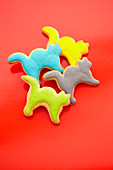 Cat shaped biscuits with colorful icing in front of a red background