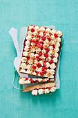 Blechkuchen mit Cremetupfen, Himbeeren und Keksstückchen