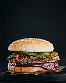 Beefsteak-Burger mit karamellisierten Zwiebeln, Essiggurken und Barbecuesauce