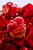 Tarts with red fruits on rose petals and red berries