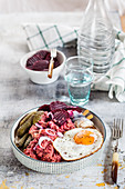 Lobscouse with soused herring, fried egg, beetroot and gherkins