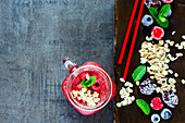 Close up of red smoothie drink in glass jar and healthy ingredients on dark chopping board over rustic background