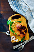 Top view of fresh fish and crab burger with sliced onion on little wooden cutting board over dark rustic background