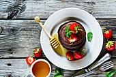 Chocolate pancakes with fresh strawberries and honey, served on ceramic plate over old grey wooden background