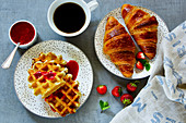 Close up of breakfast table with fresh baked croissants and waffles, served with coffee, strawberries and homemade berry jam