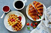 Frisch gebackene Hörnchen und Waffeln mit Kaffee, Erdbeeren und Beerenmarmelade