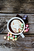 Close up of hot chocolate in white ceramic cup with whipped cream and marshmallows on rustic wooden background