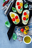 Close up of homemade tomato and basil bruschetta or sandwiches with ingredients on light grey background