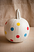 White-painted pumpkin decorated with polka-dot stickers