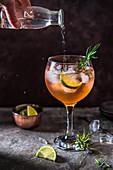 Pink Gin Cocktail mit Angostura Bitter, Limette, Rosmarin und Tonic Water
