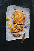 Classic Viennese veal escalope on grease-proof paper, sliced