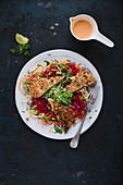 Turkey escalope with a nut crust with beetroot rice noodles, julienned carrots and a herb and cress salad
