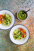 Zucchini pasta with rocket pesto and tomatoes