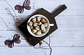 Top view of quail eggs in a white bowl on a black cutting board decorated with a bare tree branch and paper butterflies