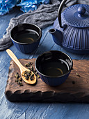 Green tea in blue cups with blue cast iron tea pot