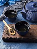 Green tea in blue cups with blue cast iron tea pot