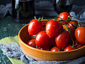 Raw tomatoes in a rustic bowl on dark background