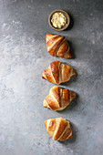 Fresh baked traditional croissant with butter in row over grey texture background