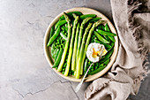 Variety of cooked green vegetables asparagus, peas, pod pea, served with bread and poached egg