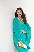 Brünette Frau in elegantem, türkisfarbenem Abendkleid