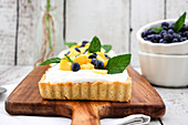 Yoghurt and coconut tart with mango, blueberries and mint