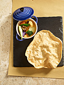 Colourful vegetable casserole with curry in a cocotte, served with flatbread (top view)