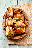 Stuffed spinach pastries in a wooden bowl
