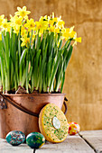 Egg-shaped Hanseatic Easter cake leaning against a copper pot of narcissi