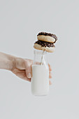 A hand holding a milk bottle with two doughnuts on a straw